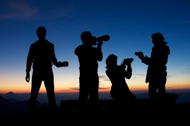Four photographers silhouetted against a sunset
