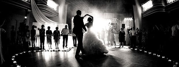 A couple's first dance in a brightly-lit, black and white photo