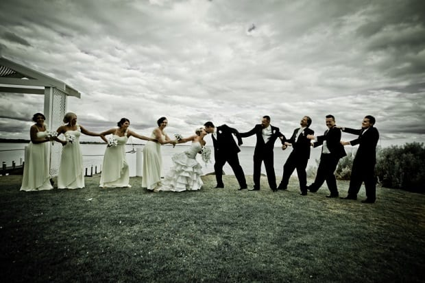 Bride, groom, and friends playing tug-of-war