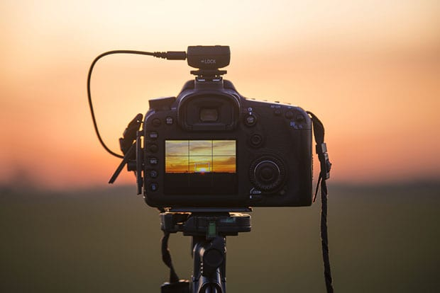Camera tripod pointed at the sunset