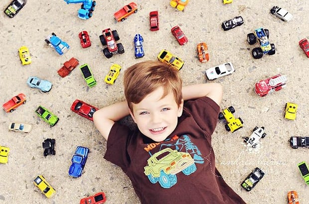 Overhead shot of a boy surrounded by toy cars