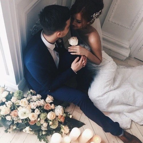 Newlyweds sit on the floor and gaze into each other's eyes.