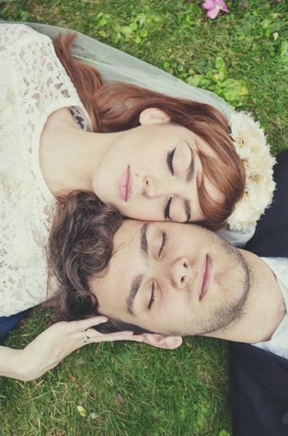Newlyweds lay in the grass, cheek to cheek.