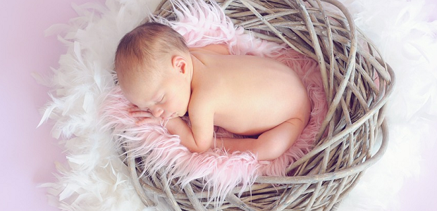 A newborn baby laying in a basket