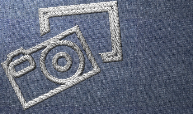 An image of a camera stitched into blue fabric