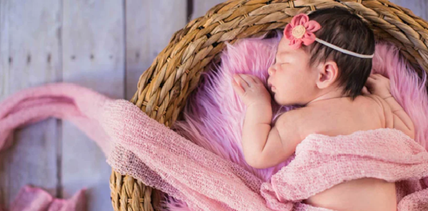 a newborn on a pink fluffy pillow in a basket
