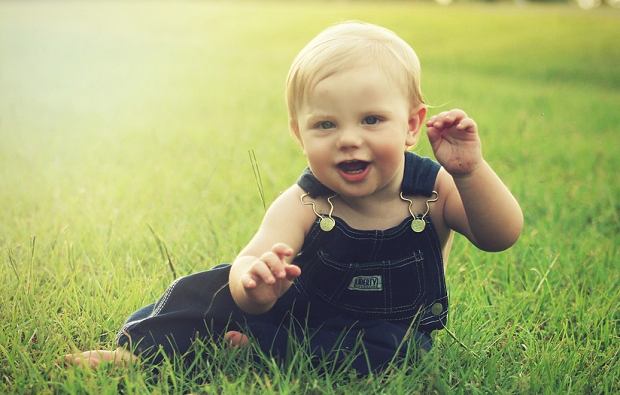 A picture of a baby sitting on the grass on a bright sunny day