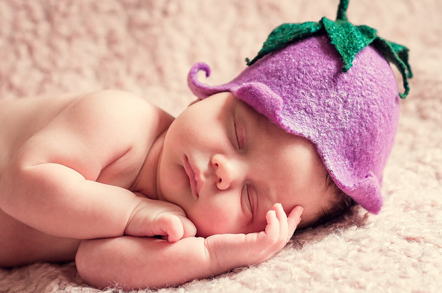 A close-up photo of a sleeping baby wearing a purple fruit hat