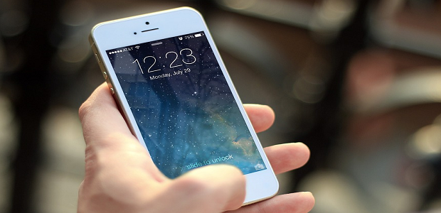 A person holding an iPhone on the lock screen, with a starry sky set as the background