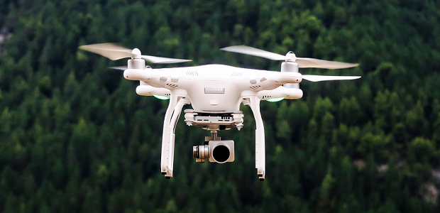 A camera equipped drone flying over a deep green forest