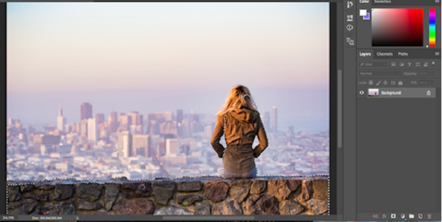 An image of a woman sitting on a stone wall overlooking a city, with the foreground carefully selected