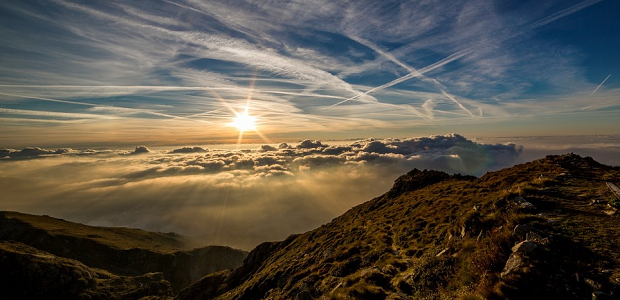 A scenic mountain view, with the sun shining brightly over some clouds