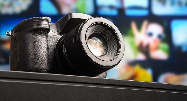 A close-up of a camera on a desk, with several screen in the background
