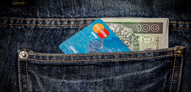 A credit card and paper money in a jeans pocket