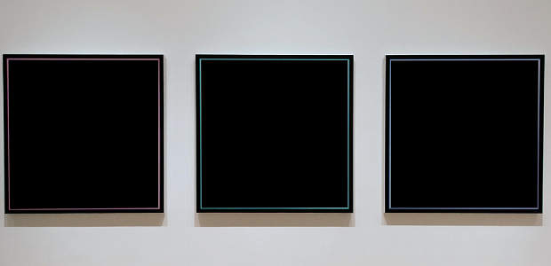 Three blank, black canvases lined up on a wall