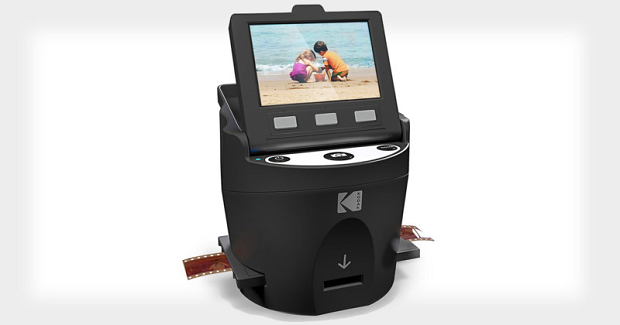A digital film scanner with a piece of film running through it, displaying an image of kids on a beach
