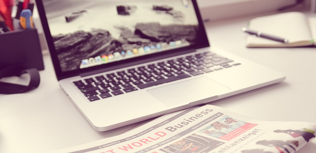 A toned-down image of a newspaper sitting on a table in front of an open laptop