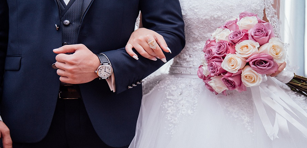 A groom and bride linking arms