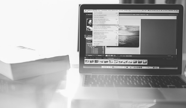 A black and white image of a laptop, with photo editing software open and in use