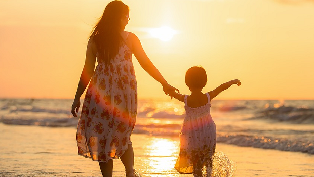 A mom and her daughter taking a stroll on the beach in front of the sunset