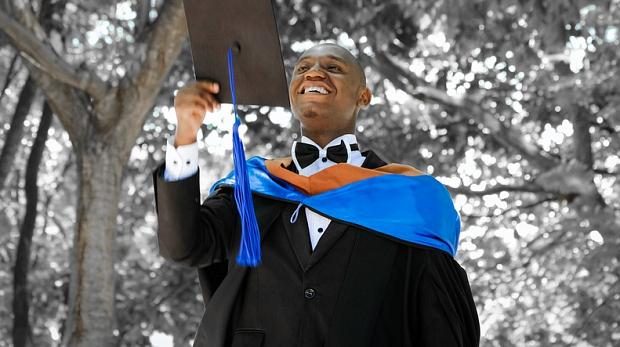 A graduating student holding up his graduation cap