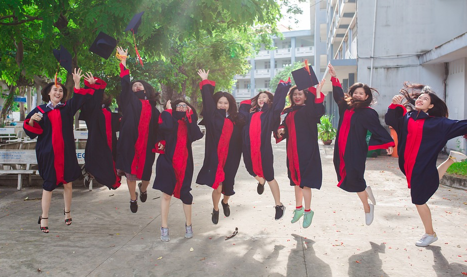 A lined up group of graduates in black and red gowns jumping and throwing their hats