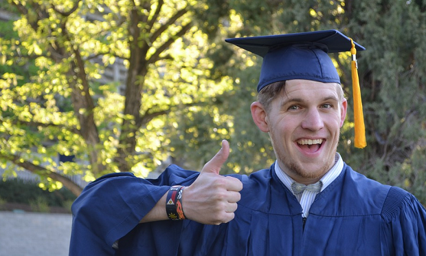 A man in a blue graduation gown giving a thumbs up