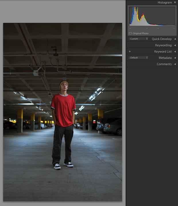 Man in jeans and a red t-shirt standing in the center of a parking garage with cars on either side of him.