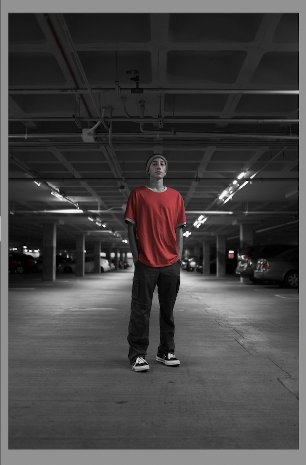 Original image appears black and white, except for red tones in the man's shirt, face, and in the taillights of some cars in the background.