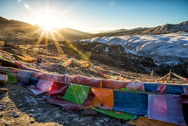 Sun glaring over mountains with colorful fabric strung in the foreground