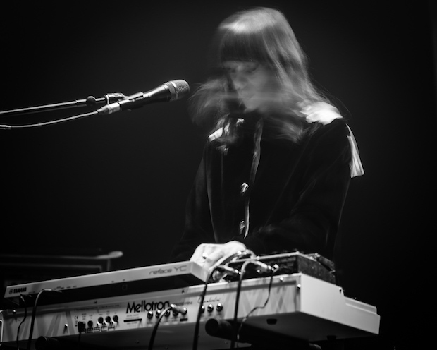 Keyboardist whose face is blurred in motion. Her keyboard and microphone are crisp in the shot.