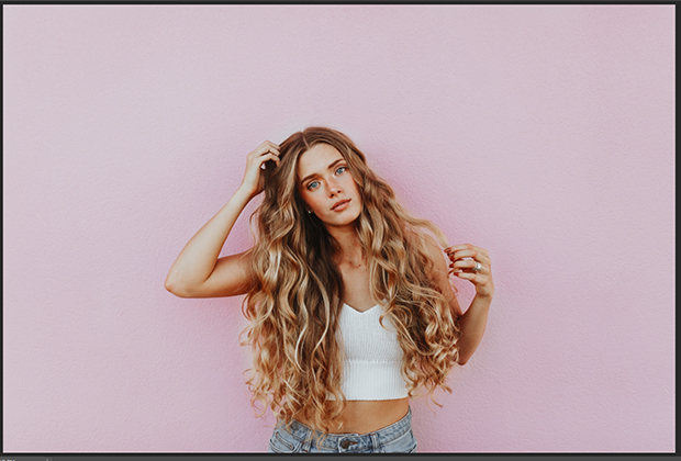 Portrait of blonde woman against pale pink background