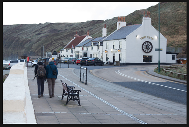 """Seaside pub named """"The Ship"""" on the right with travelers walking toward it on the left"""