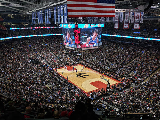 Crowded basketball sports arena featuring basketball court, jumbotron coverage, and fans in seats