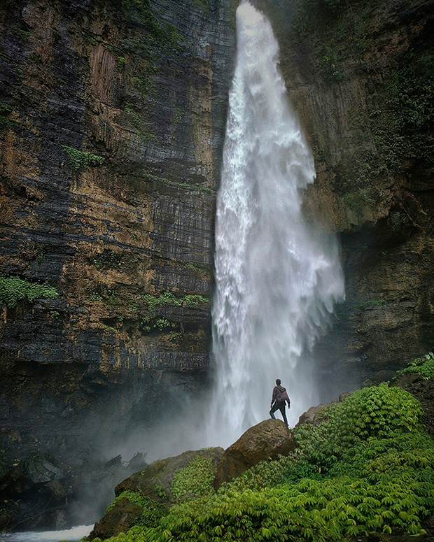 Figure standing in front of a tall waterfall