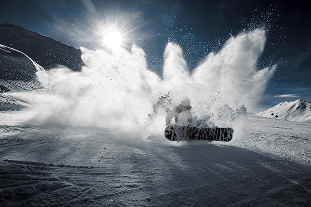 Snowboarder spraying snow on a trick